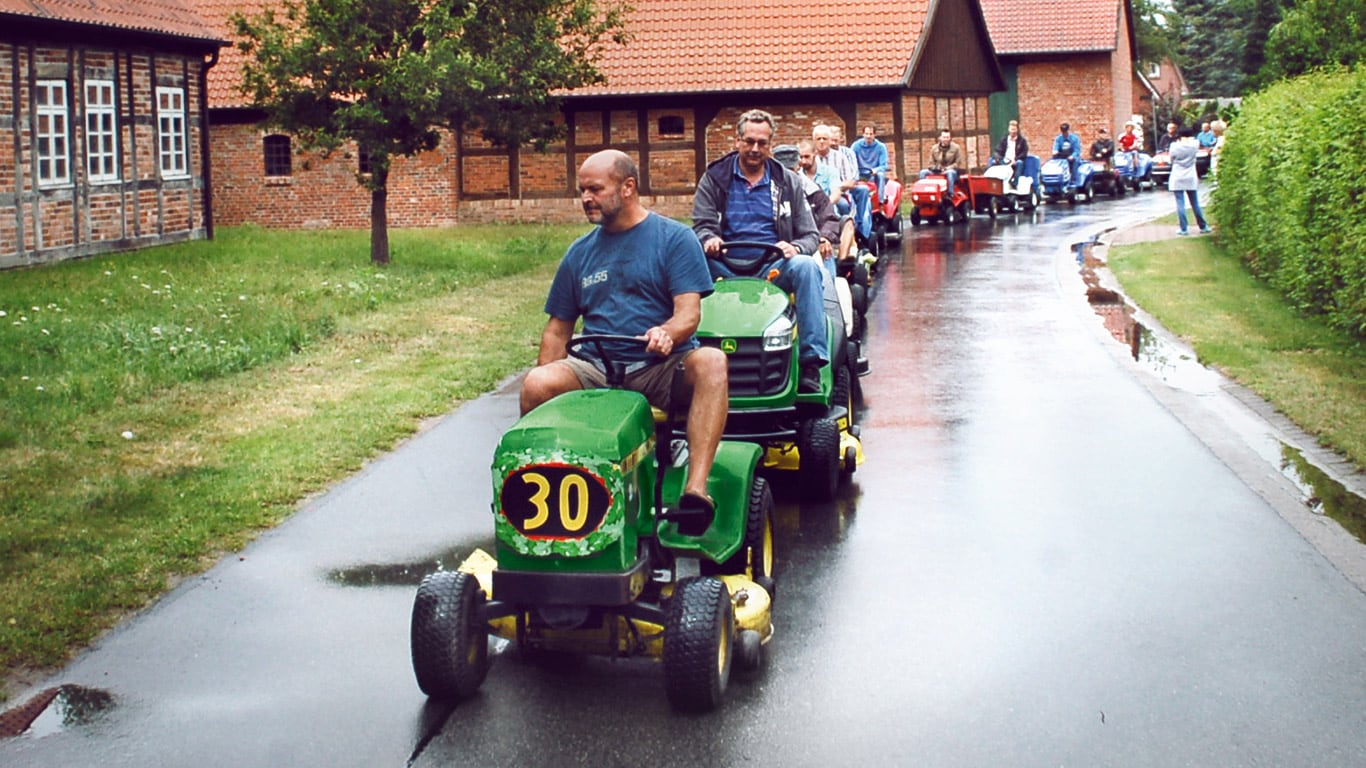 Oude zitgazonmaaier, huiseigenaar, dorp, parade