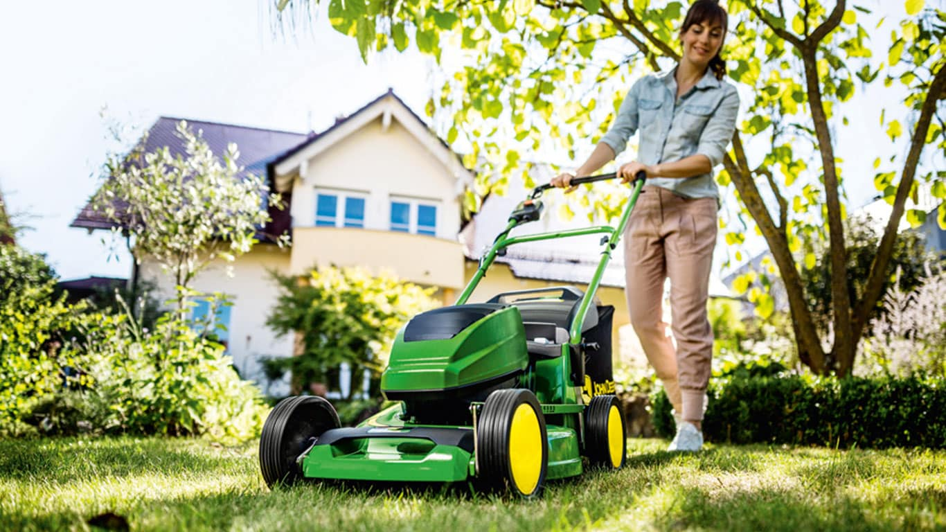 Woman with John Deere R43B Walk-Behind Mower in the garden